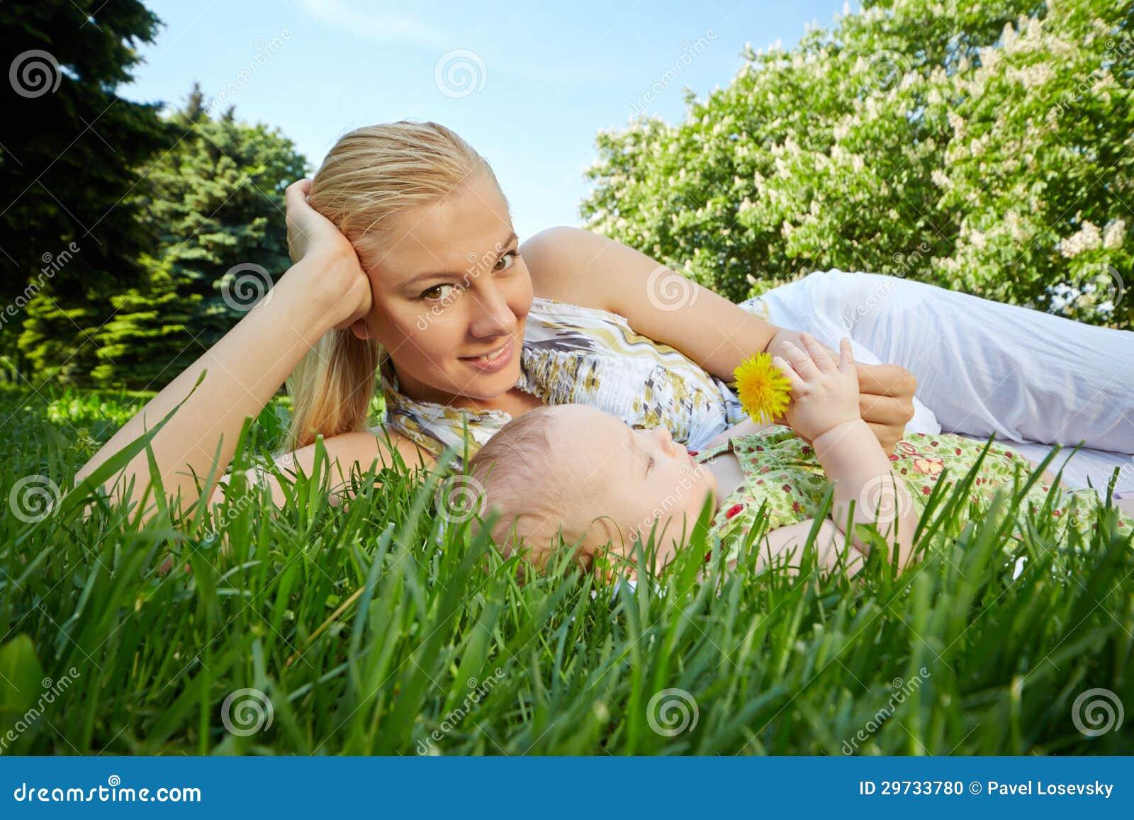 年轻母亲在绿草斜倚在她的婴孩旁边