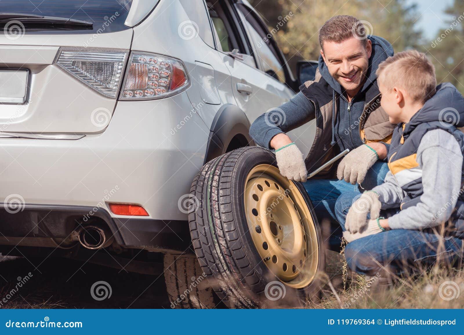 微笑的父亲和儿子改变的汽车