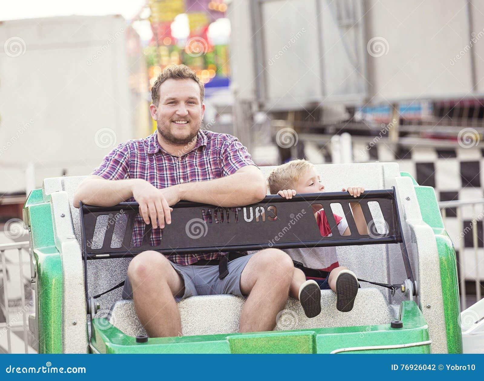 微笑的父亲和儿子游乐园的一起乘坐