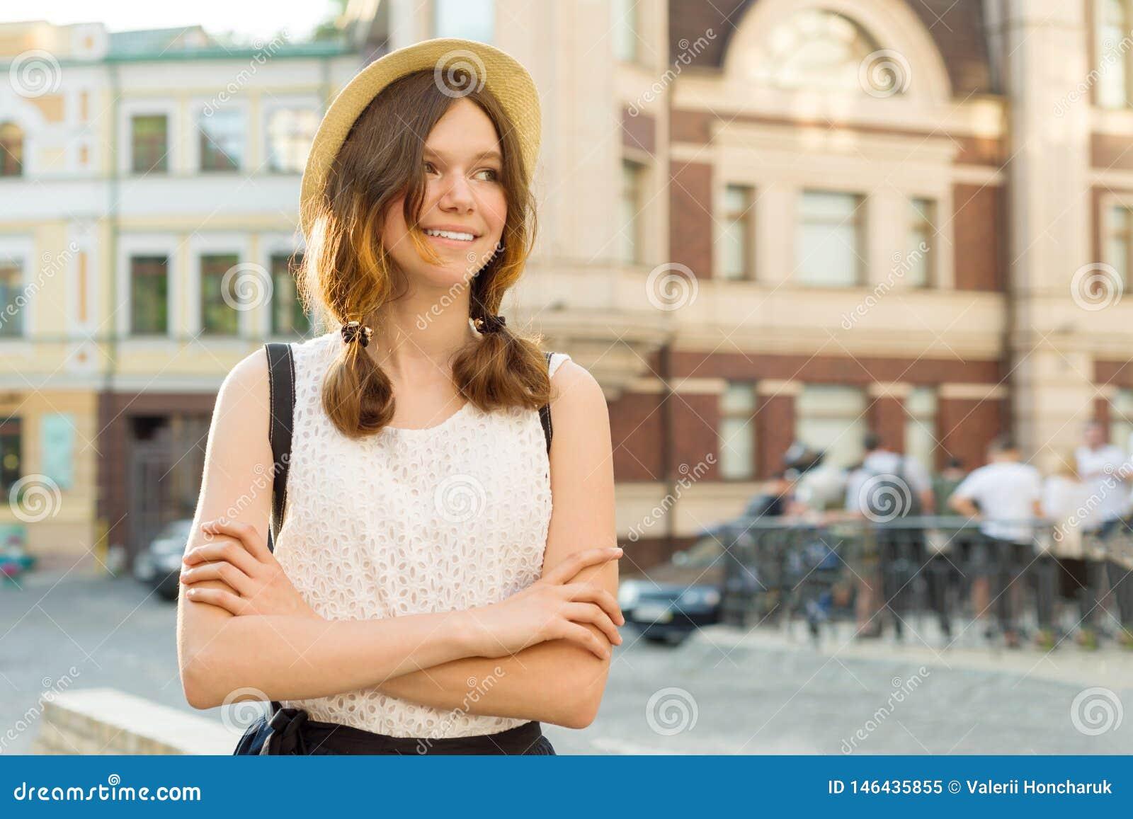 微笑的美丽的少年女孩13,戴在城市街道上的14岁夏天室外画象帽子,拷贝空间