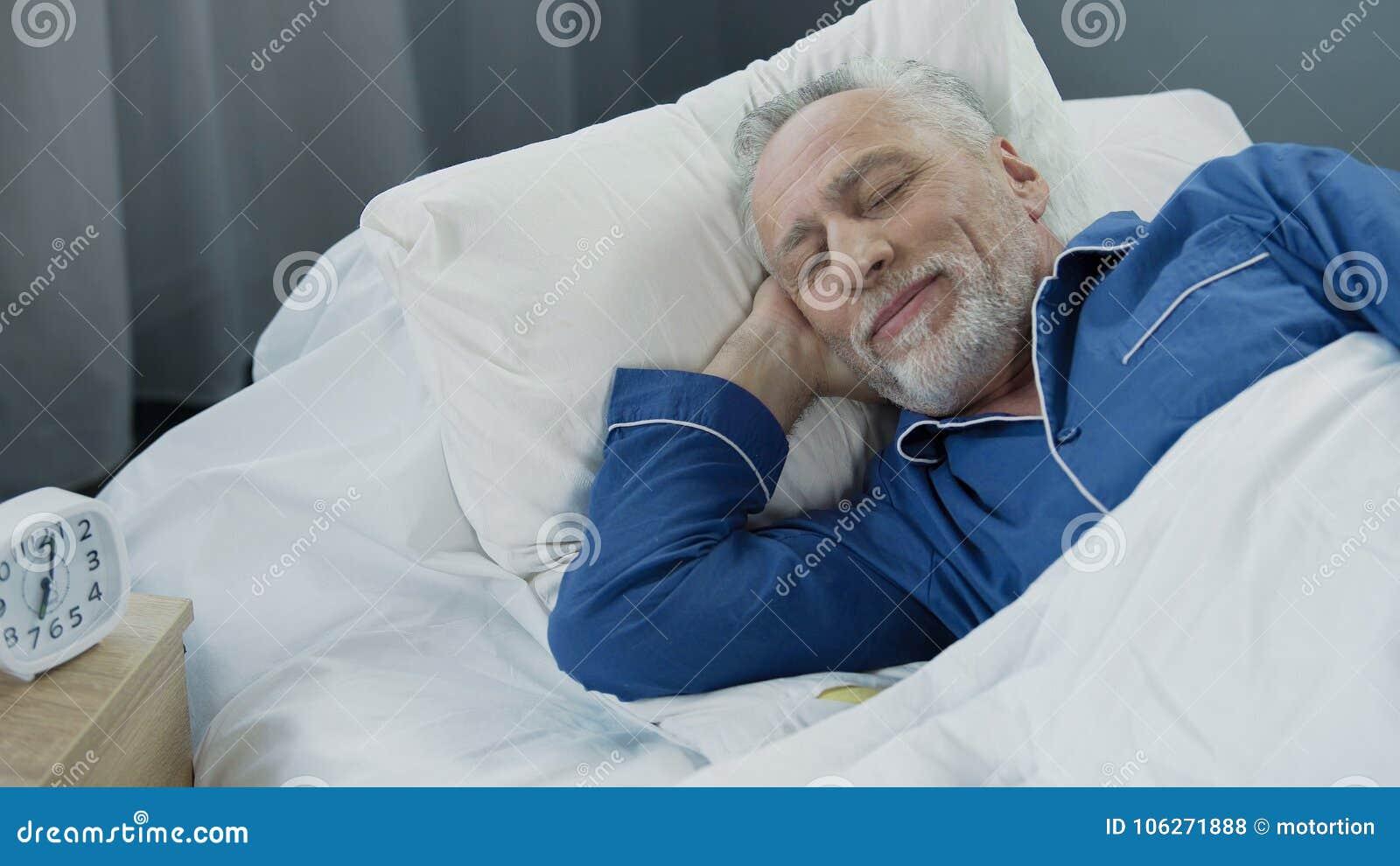 微笑的老人,当睡着早晨,在床上时的喜悦的领抚恤金者