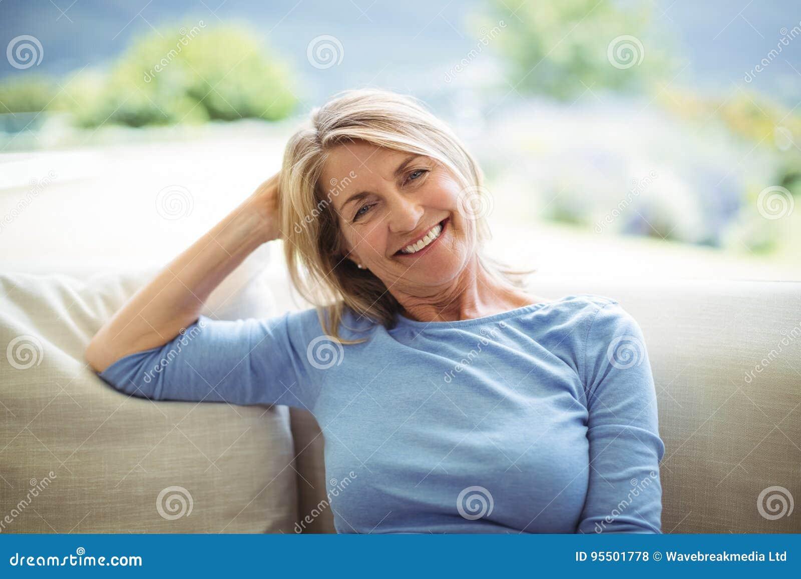 微笑的资深妇女画象坐沙发在客厅
