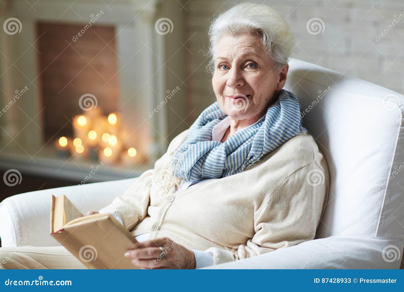 微笑的退休的妇女阅读书