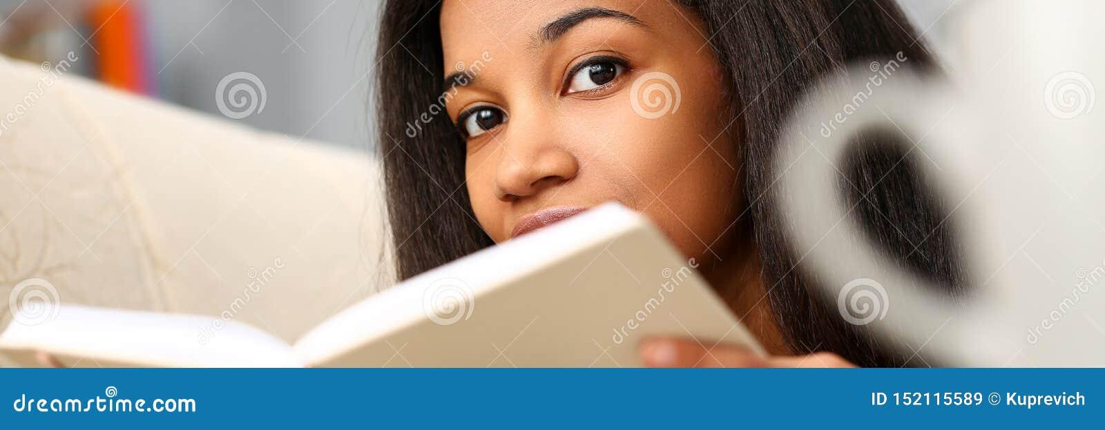 微笑的黑人妇女在家读了故事书