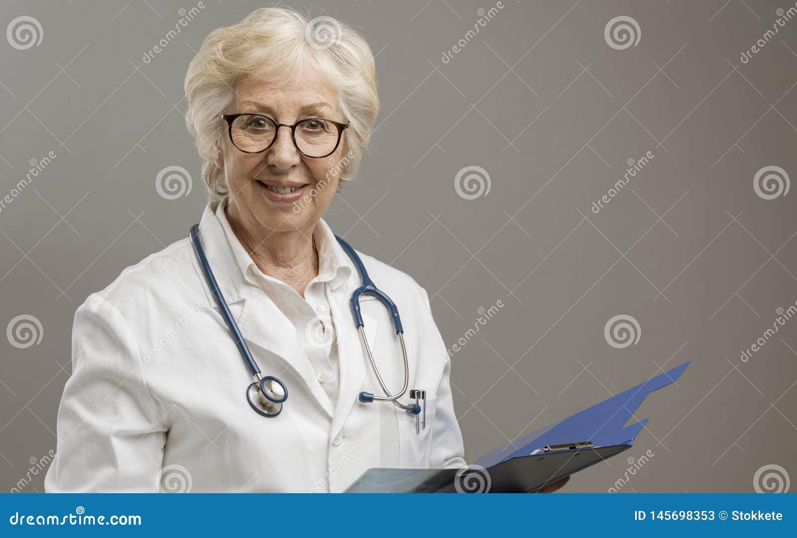 微笑确信的资深女性的医生摆在和
