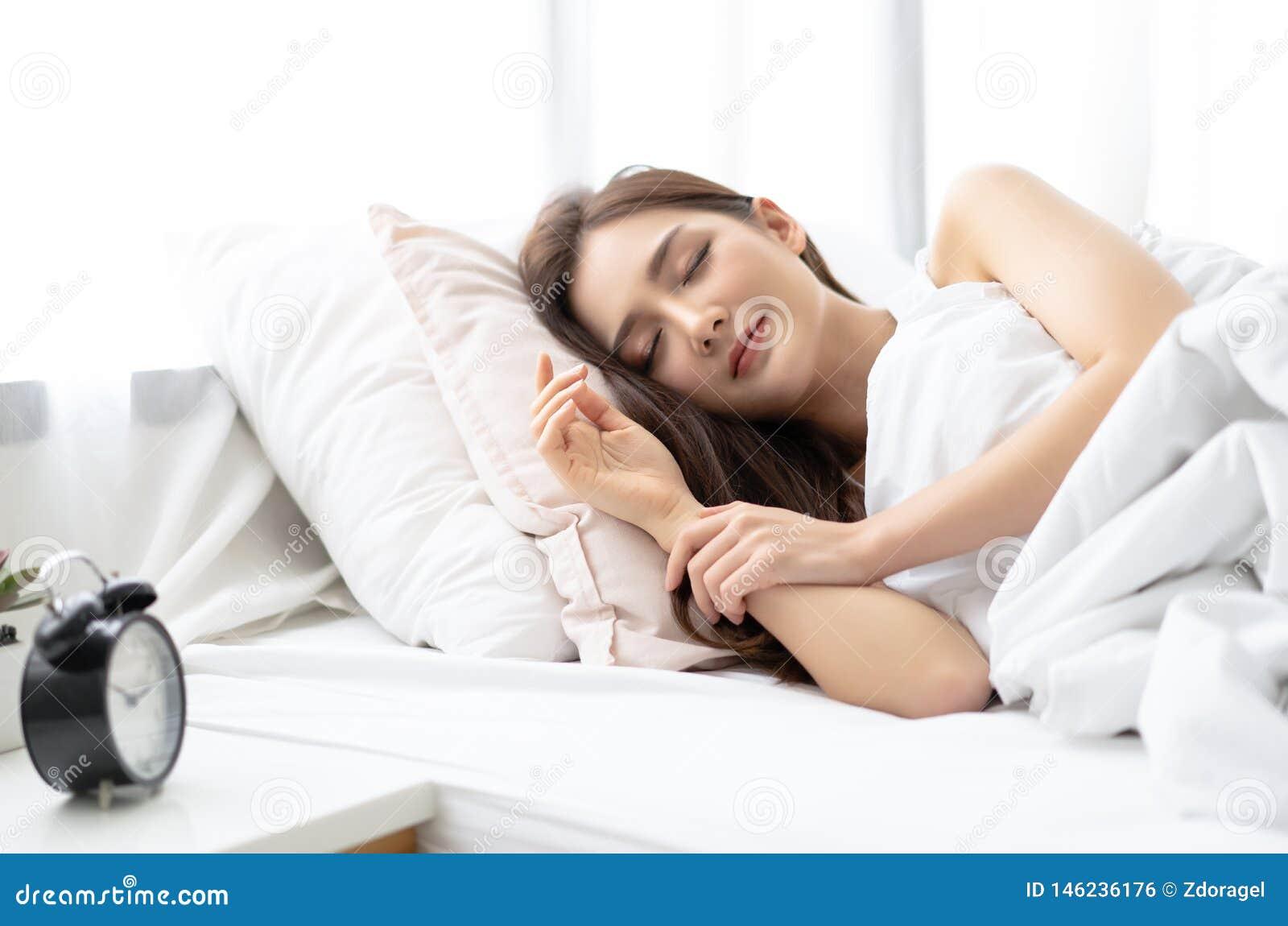 微笑美丽的年轻亚裔的妇女侧视图,当睡觉在她的床上和放松早晨时 享受晚安的夫人