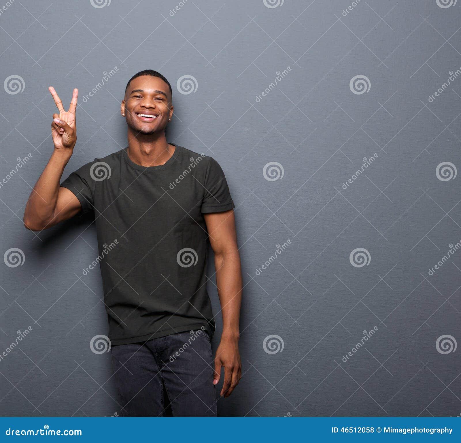 微笑年轻的人显示手和平标志