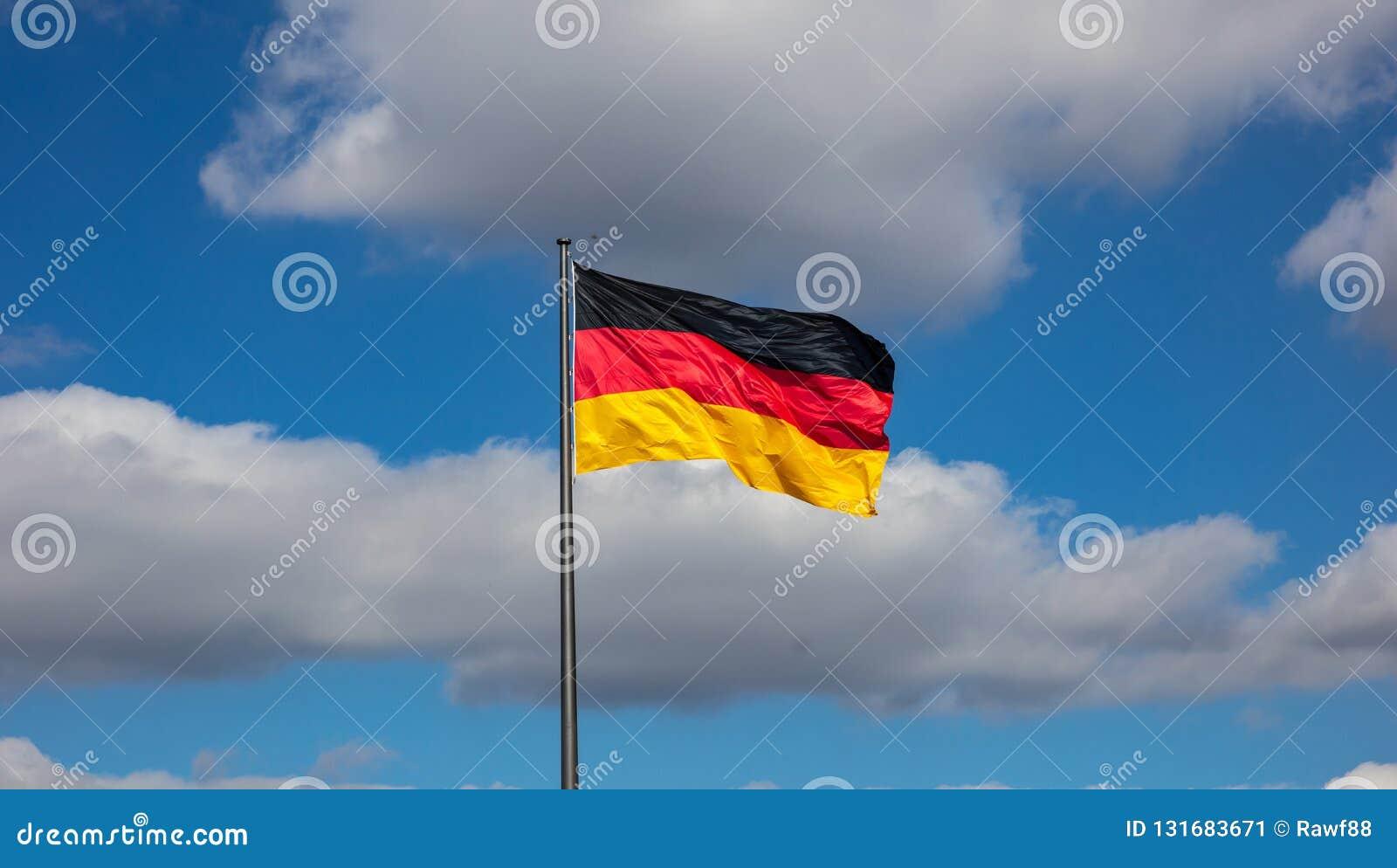 德国沙文主义情绪在反对天空蔚蓝的一个旗杆与云彩,