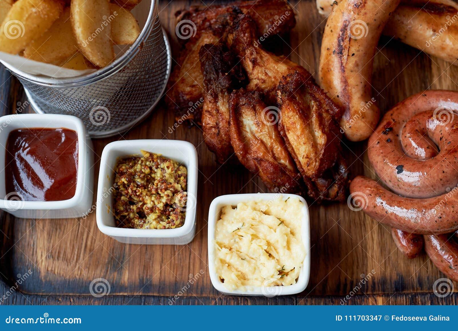 德国热诚的午餐在客栈 烤香肠,被炖的圆白菜,油煎方型小面包片,调味汁 啤酒快餐