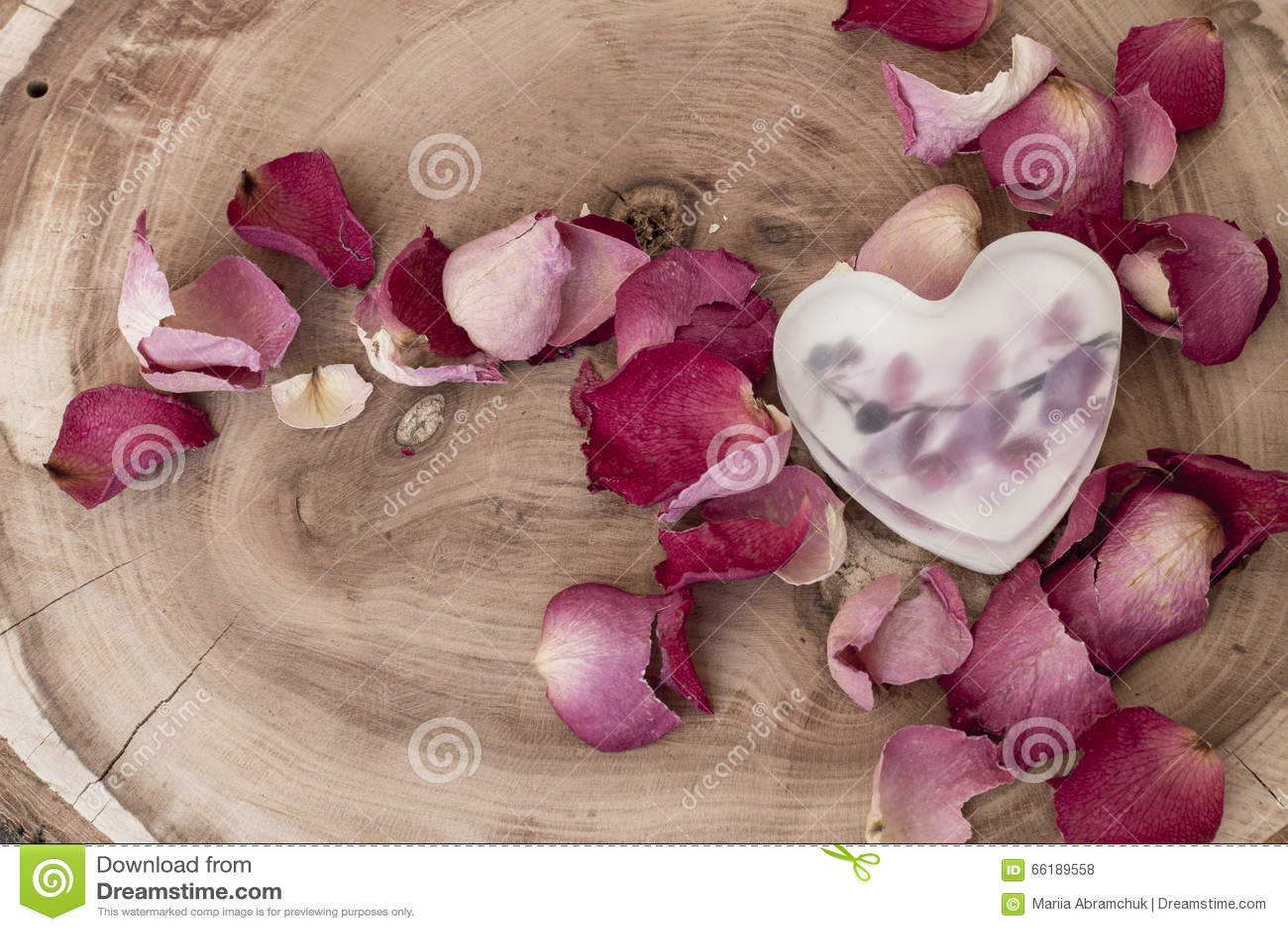 以心脏的形式肥皂在木背景的玫瑰花瓣中