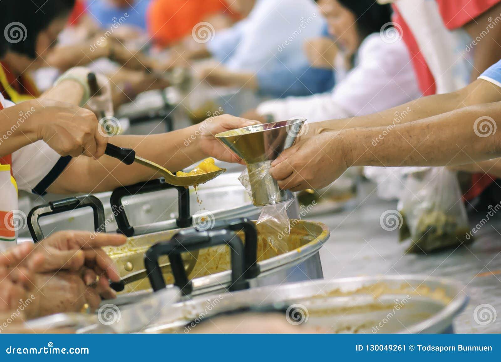 志愿者对解除饥饿的贫寒的份额食物:慈善概念