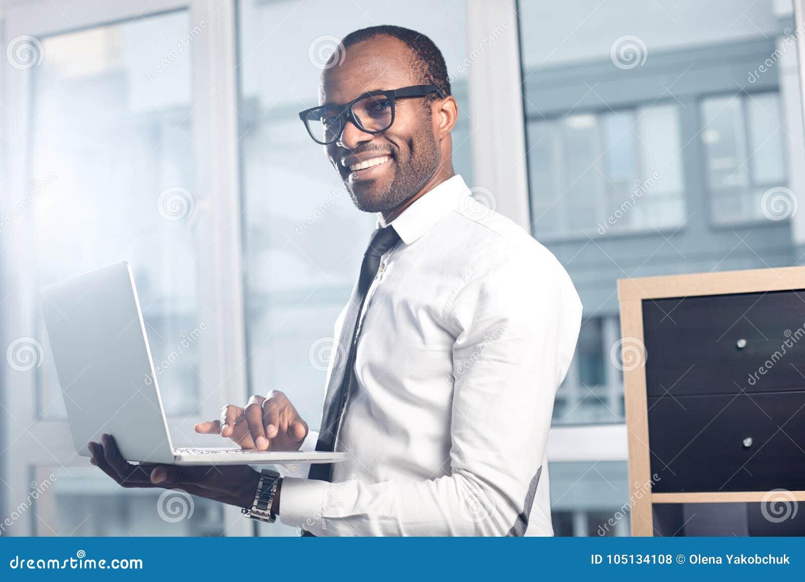 快乐的专业商人在笔记本键入