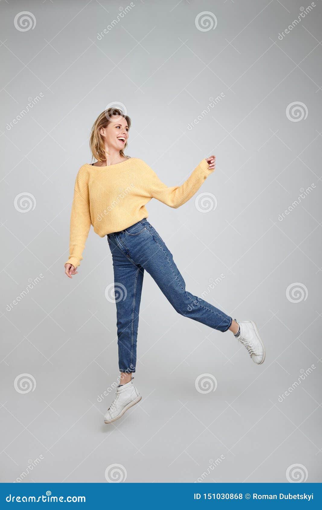 快乐的喜悦的年轻女性式样跃迁全长身体射击愉快地在反对白色背景的空气,佩带,运动衫,牛仔裤