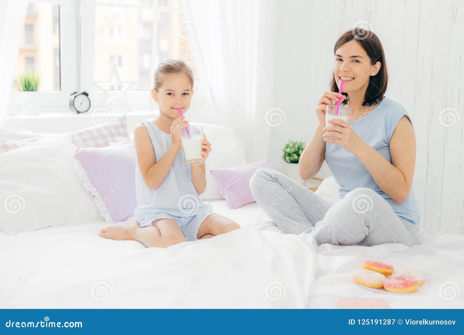 快乐的在睡衣打扮的母亲和女儿,吃早餐在早晨,饮料奶昔用多福饼,盘的腿坐c