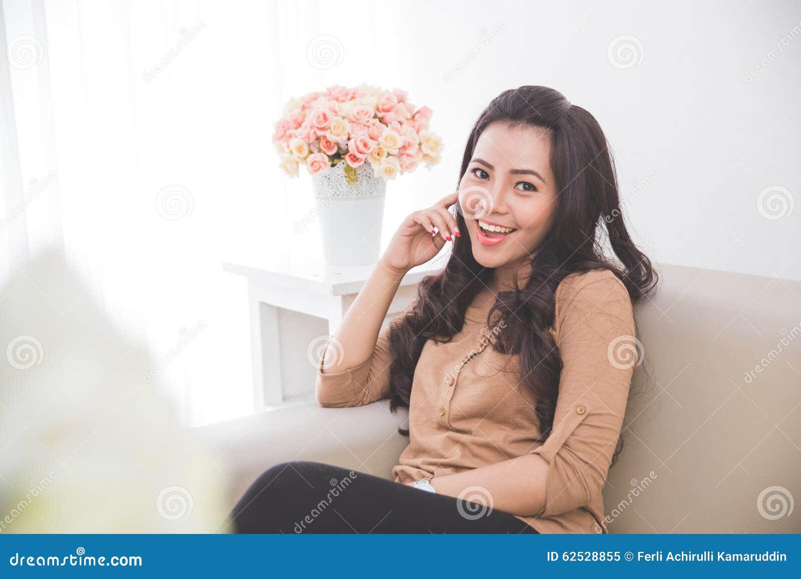 快乐的妇女坐长沙发