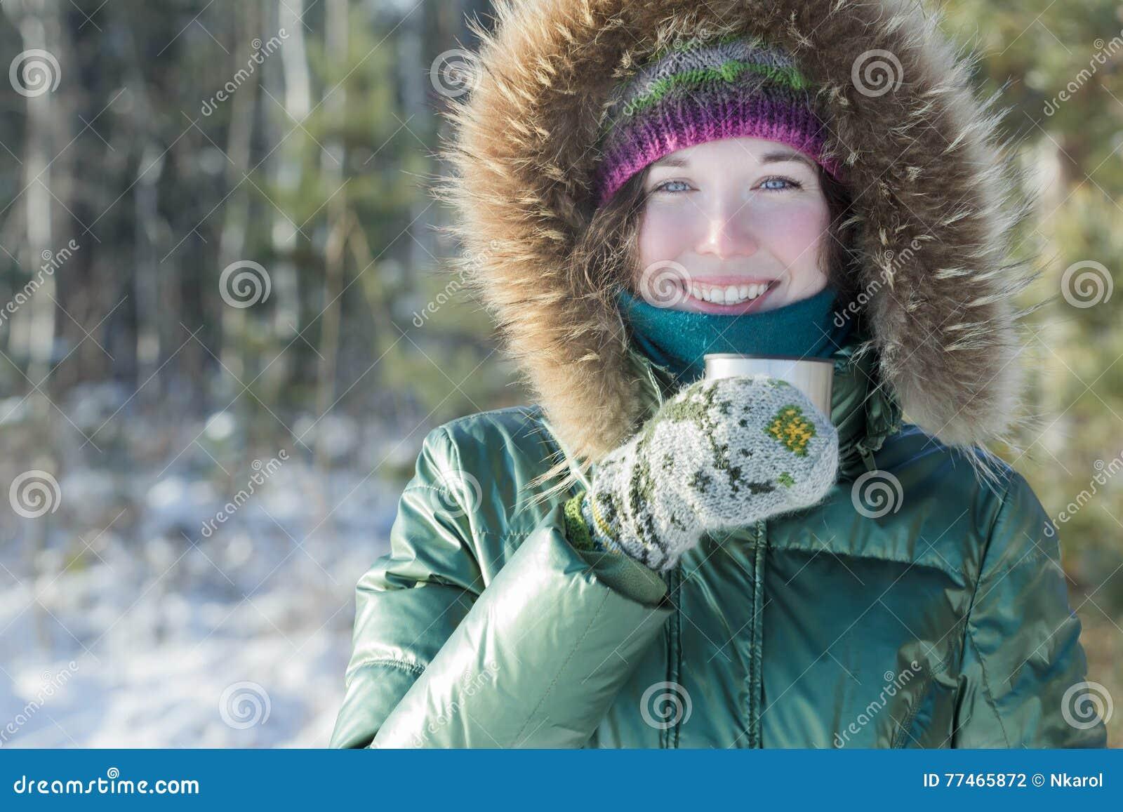 快乐的少妇在拿着不锈钢热水瓶烧瓶旅游杯子的冬天森林里户外