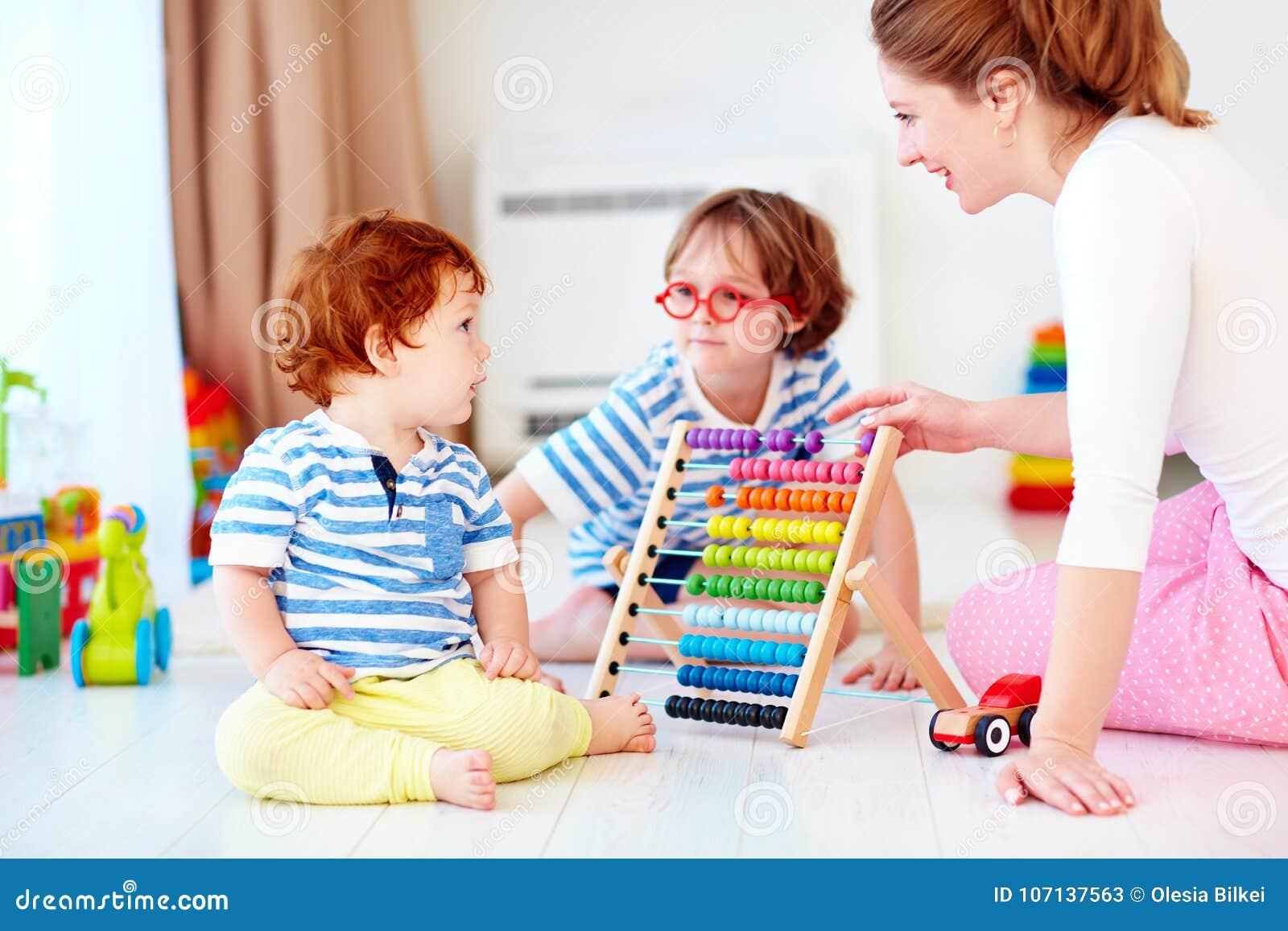 快乐的少妇,打与孩子的母亲比赛在托儿所室