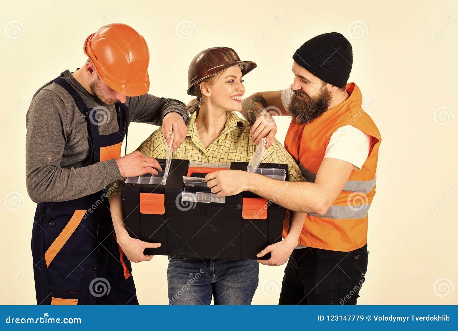 快乐的工作者公司,建造者,修理匠,石膏工 男人和妇女有微笑的面孔的在盔甲和boilersuit