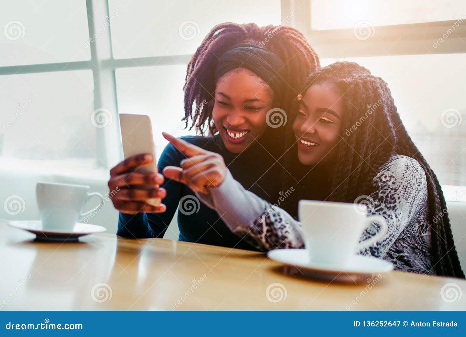 快乐的年轻非洲妇女一起坐 他们在白色电话微笑并且指向 模型坐ar bringht窗口