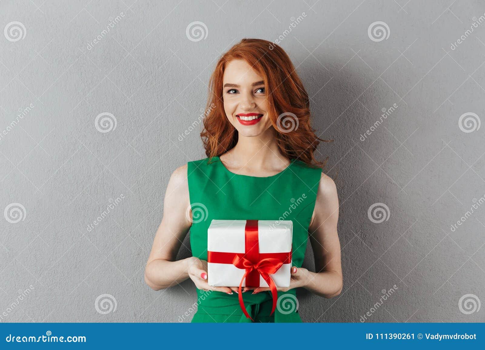 快乐的拿着礼物的绿色礼服的红头发人少妇