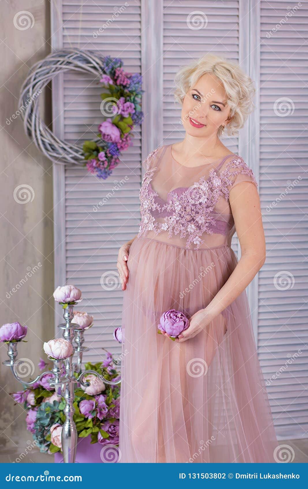 怀孕、母性和愉快的未来母亲概念-通风紫罗兰色礼服的孕妇有反对五颜六色的花束花的