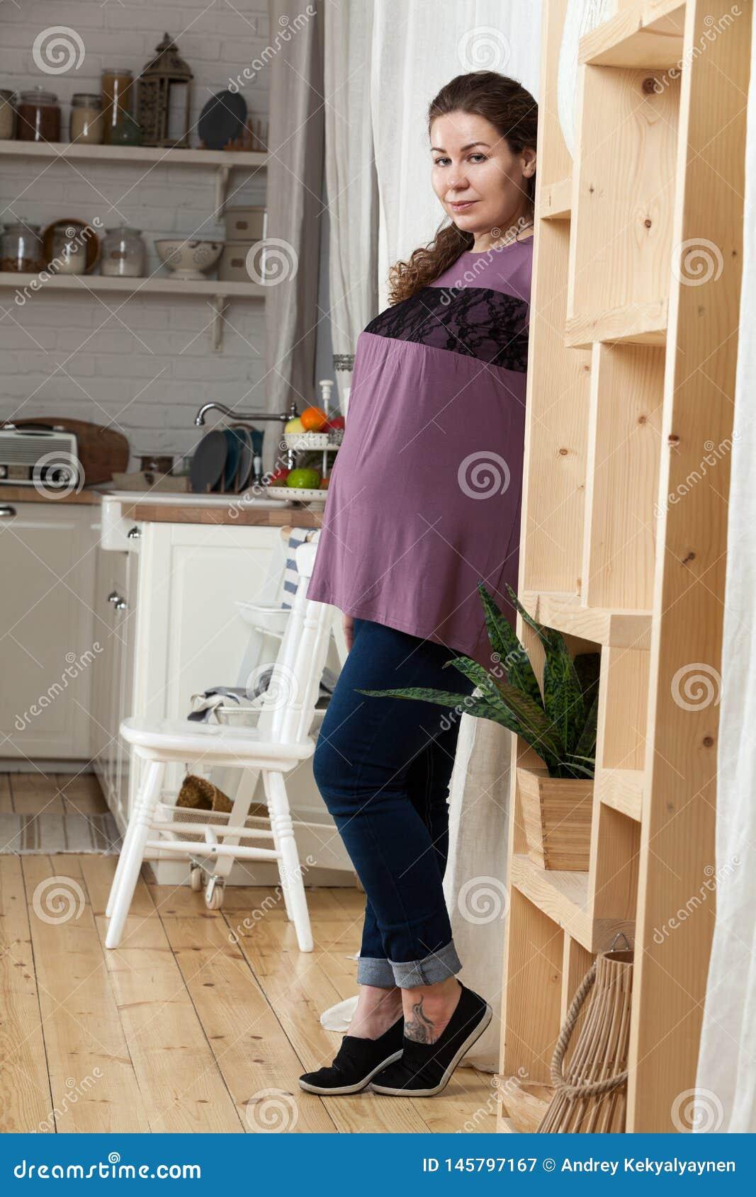 怀孕的欧洲妇女身分在厨房里,看照相机,全长画象