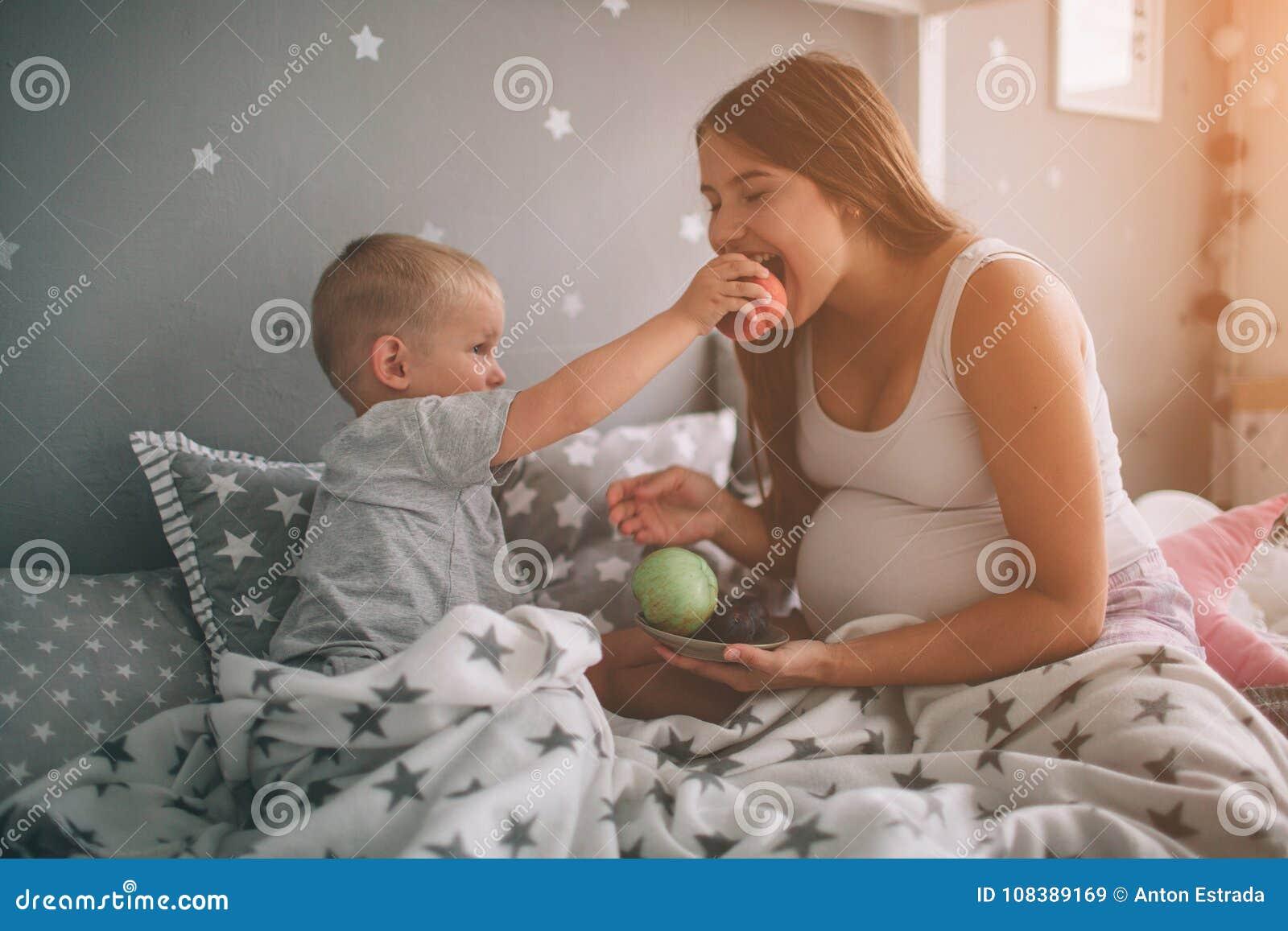 怀孕的母亲和小男孩儿子在床t家吃着一个苹果和桃子早晨 偶然生活方式