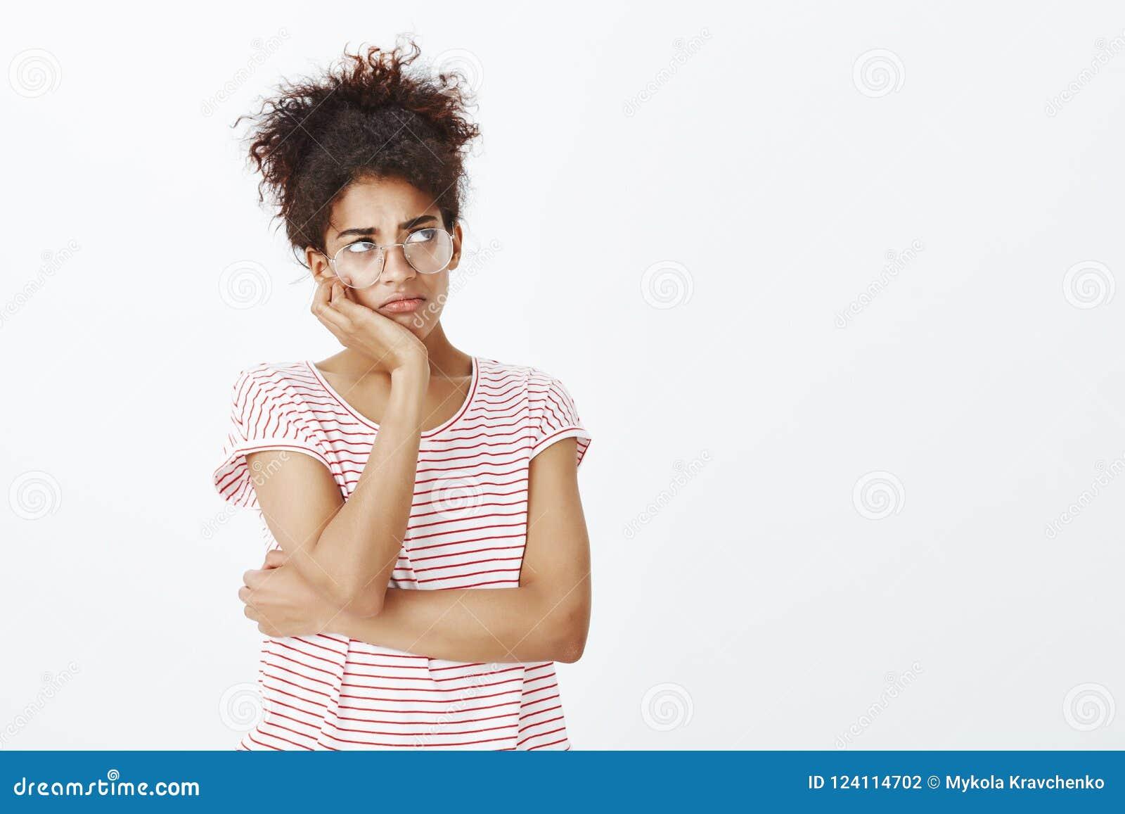思乡病和乏味的女孩feleing 阴沉的逗人喜爱的妇女画象玻璃和镶边T恤杉的,倾斜的头在手边和