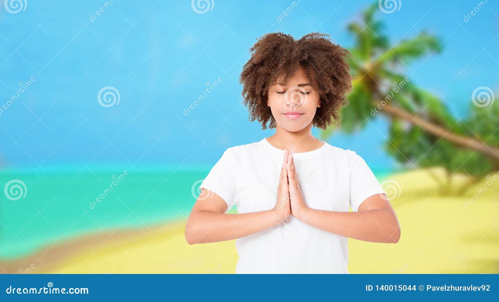 思考在与闭合的眼睛的海滩的年轻非洲的妇女 与眼睛的瑜伽asana关闭了 妇女在凝思时用namaste手