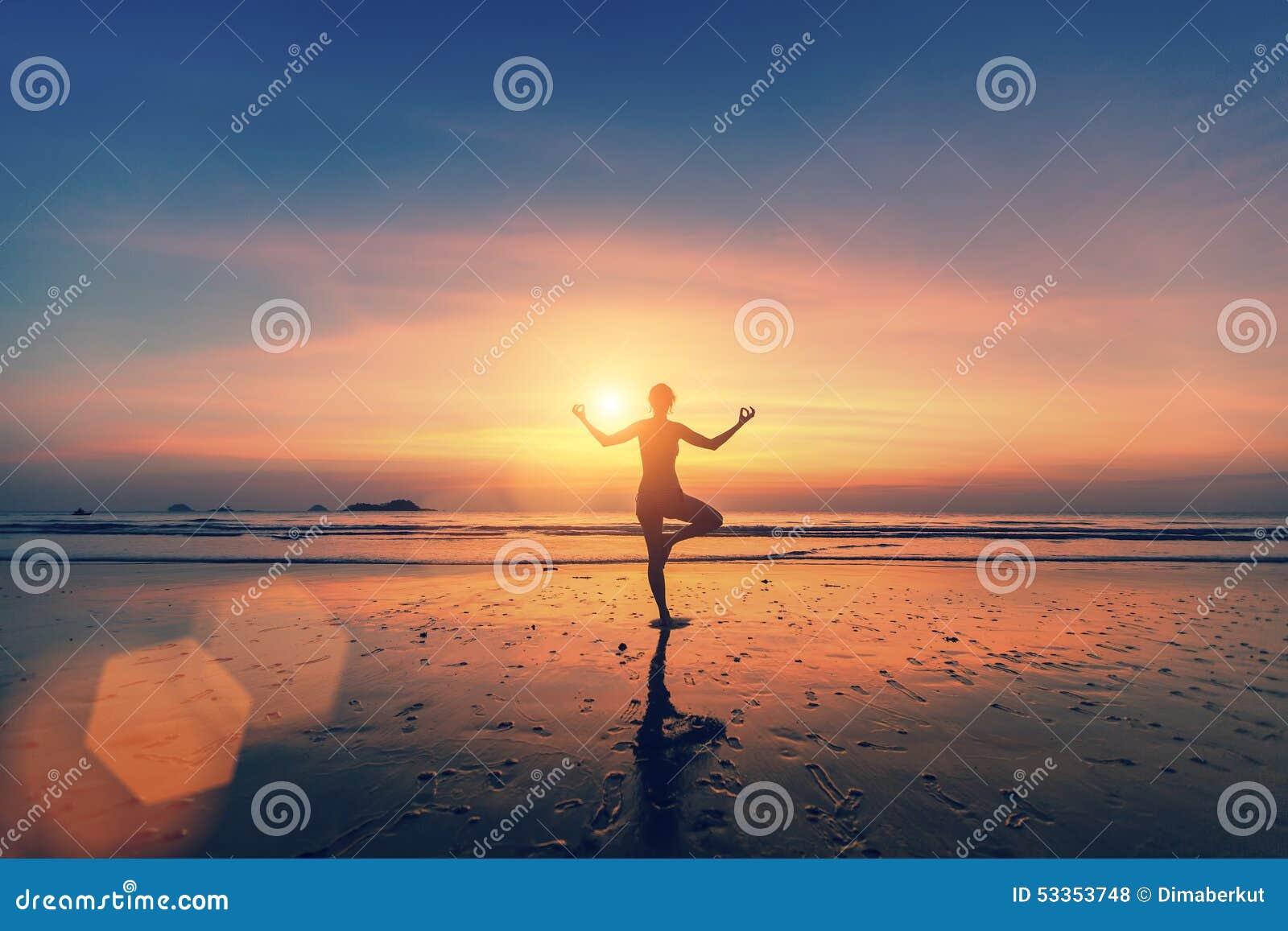 思考在海海滩的妇女剪影 瑜伽和健身.图片