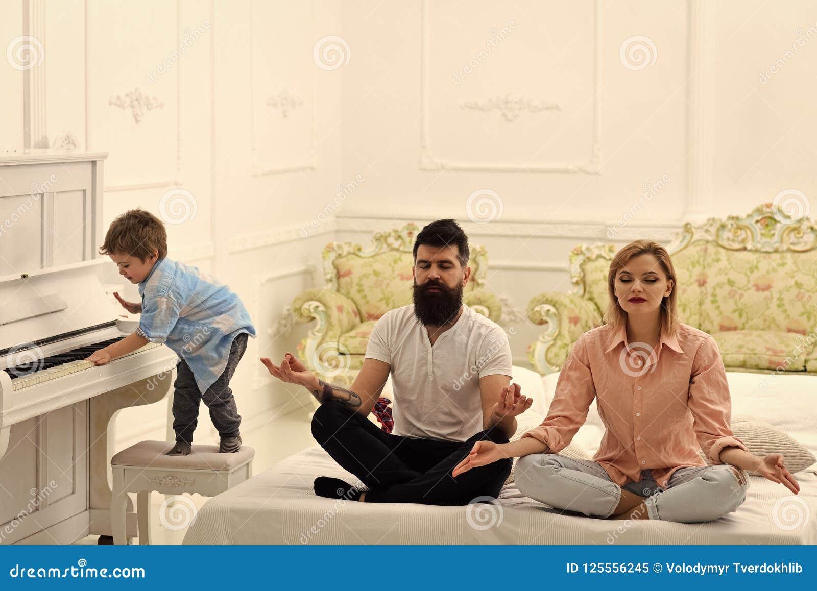 思考年轻的父母,当他们的弹钢琴,讨厌的父母时的小儿子 夫妇在床上做瑜伽锻炼 孩子