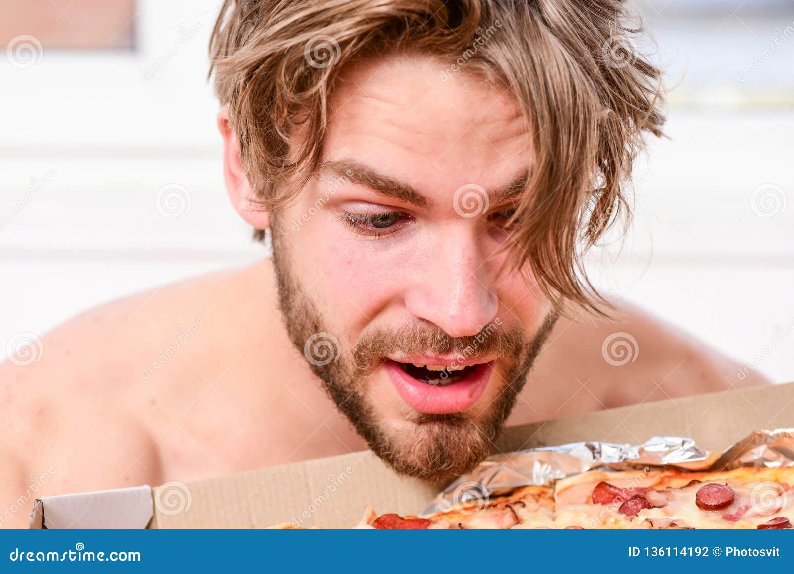 性感的人吃说谎在床上的比萨 在家是在一栋明亮的公寓的床上吃一鲜美比萨的学生 有胡子的人