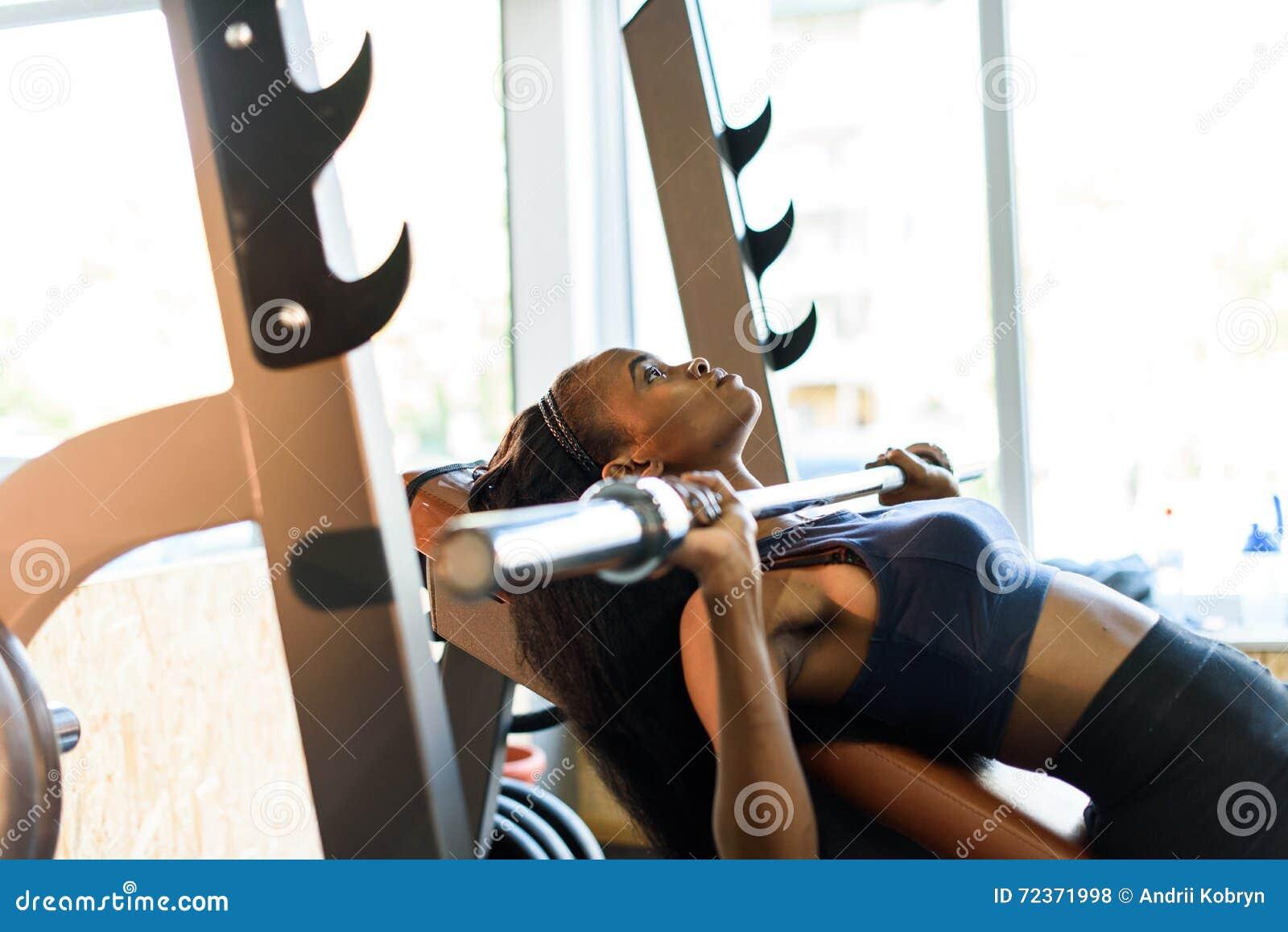 性感的华美的非裔美国人的妇女训练侧视图与杠铃的在健身房