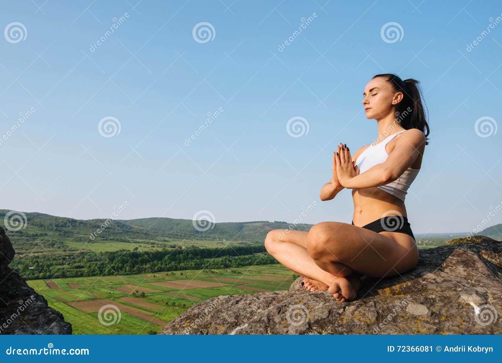 性感的少妇画象sporrtswear实践的瑜伽的在峭壁 绿色山风景背景