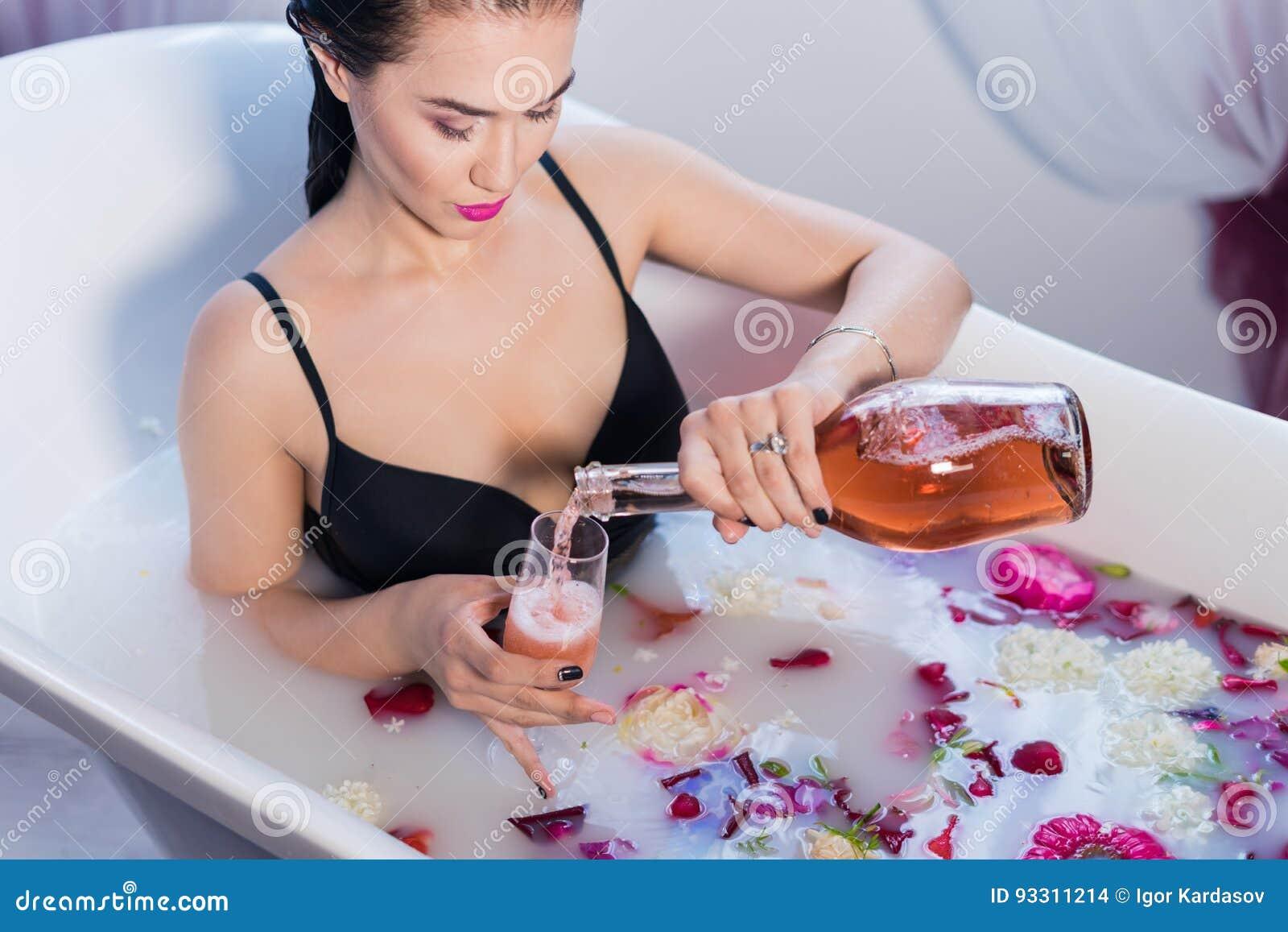 性感的深色的在浴的妇女倾吐的香槟