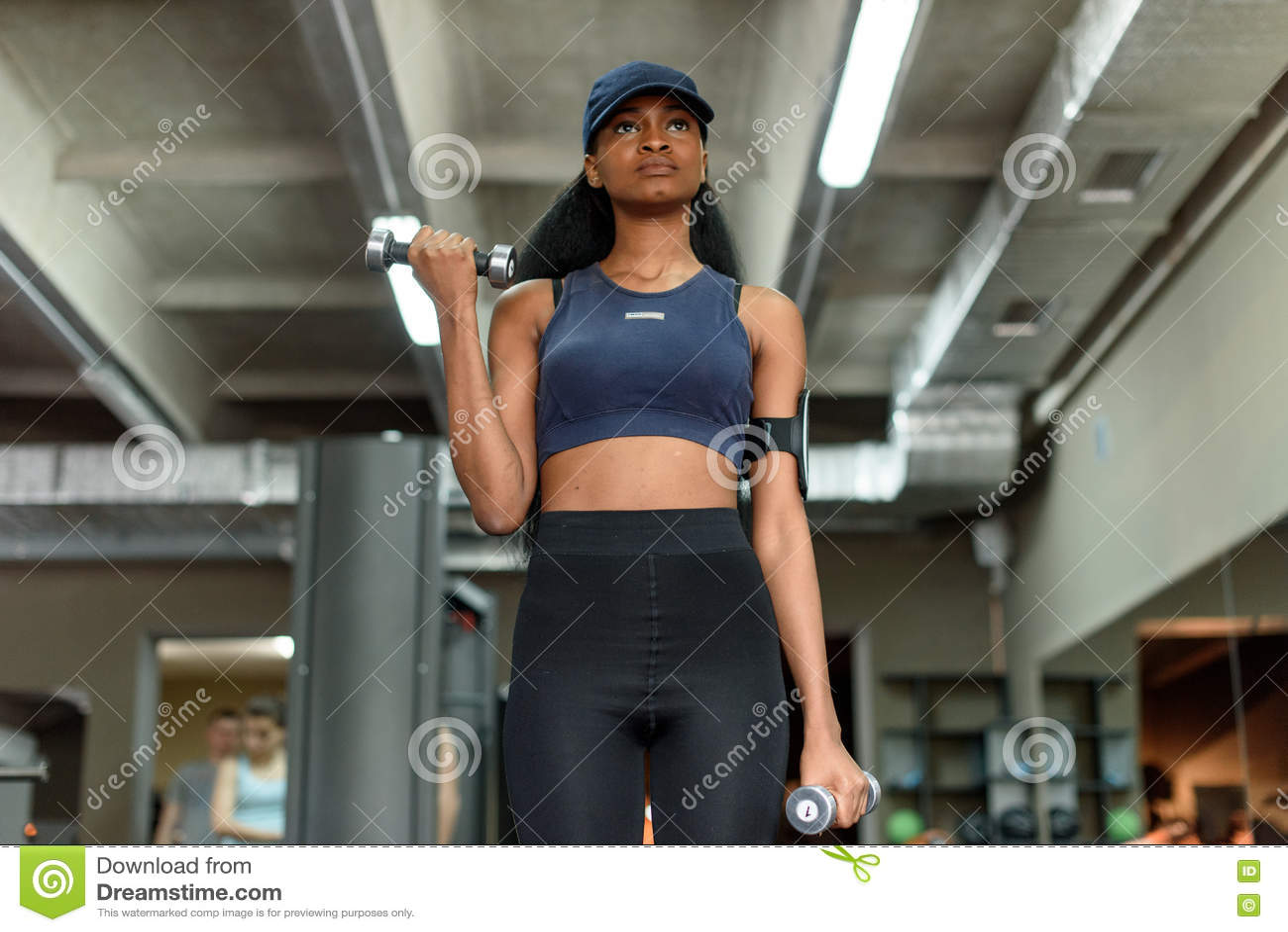 性感的解决与哑铃的健身非裔美国人的妇女在健身房