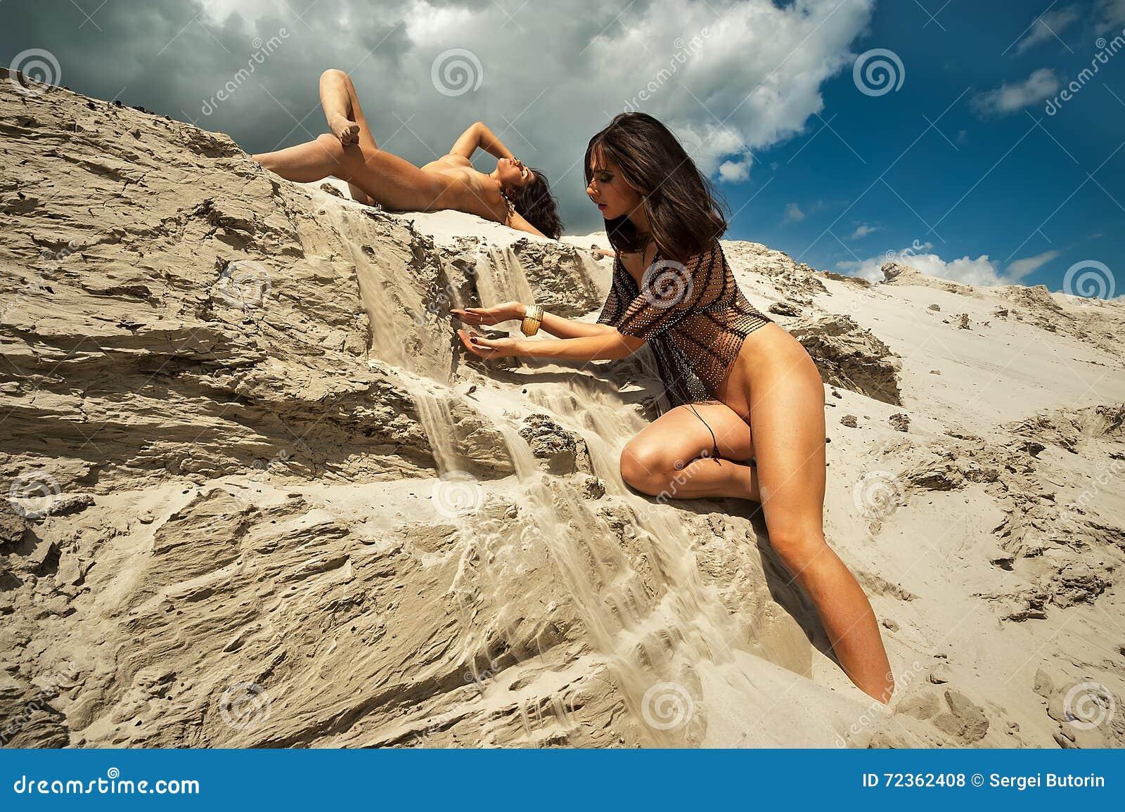 性感的赤裸妇女在流动的沙子放松