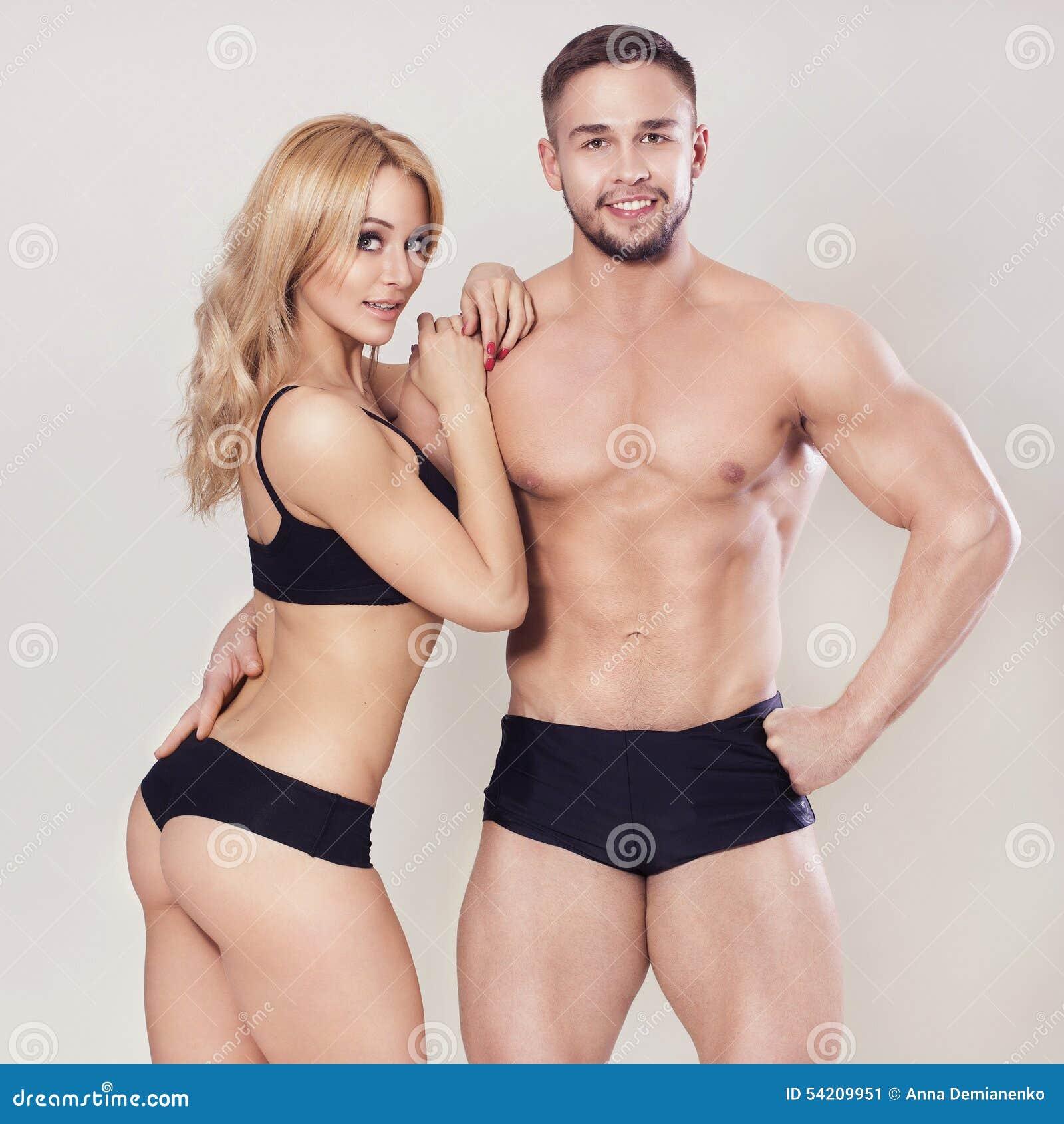 性感的适合干涉了在运动服的夫妇在中立灰色背景