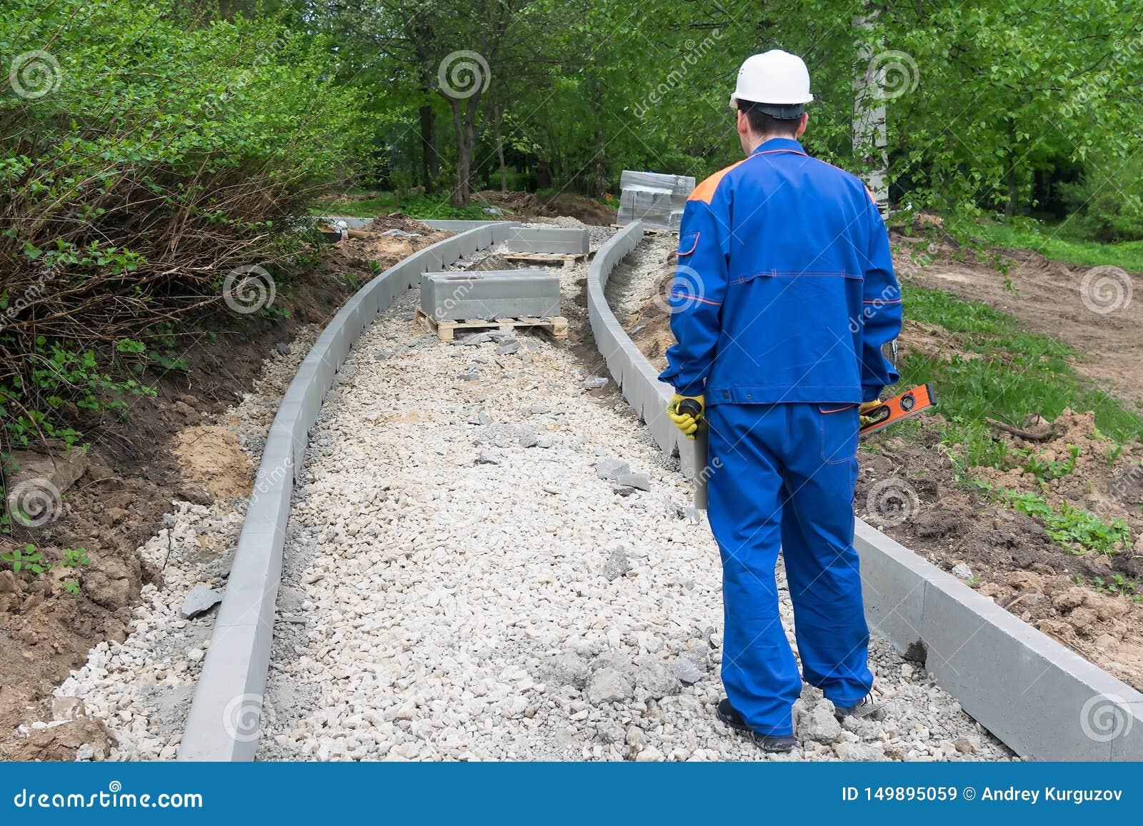 总体的一个人在他的手和步行上拿着一个修造的水平沿一条未完成的路