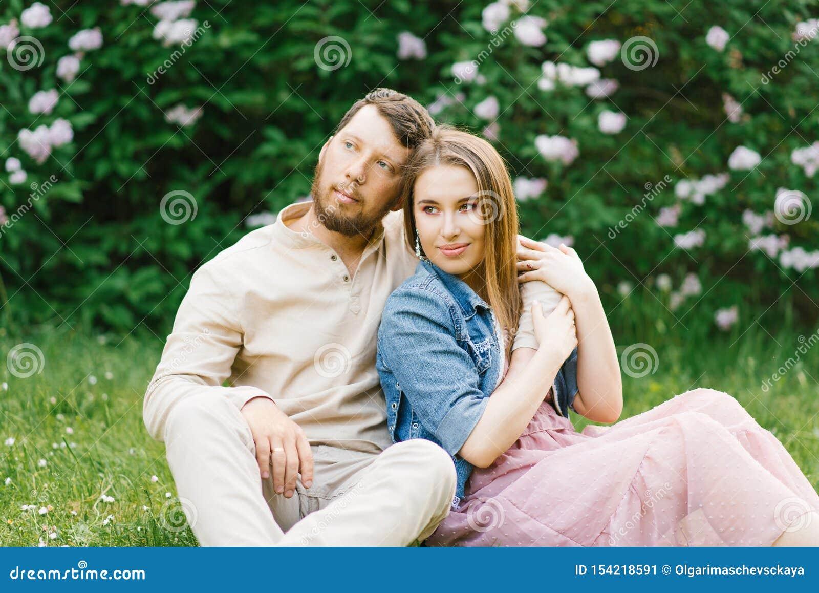 恋人新婚佳偶在一个浪漫日期在春天坐草