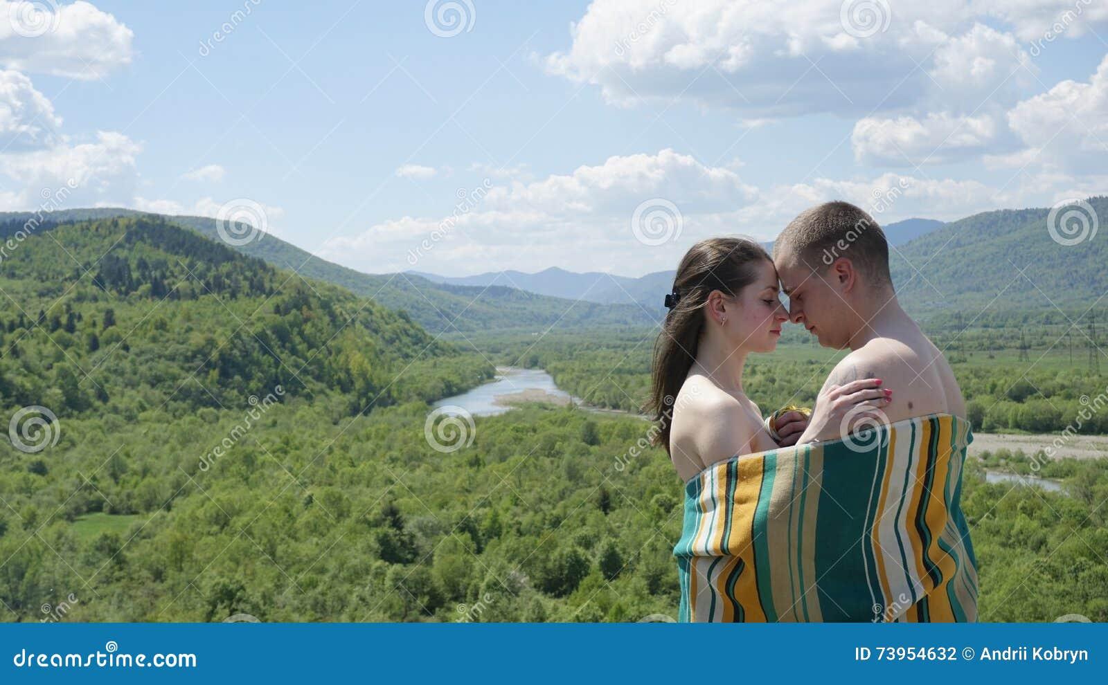 恋人 毯子报道的赤裸夫妇拥抱 人拥抱绿色山背景的女孩