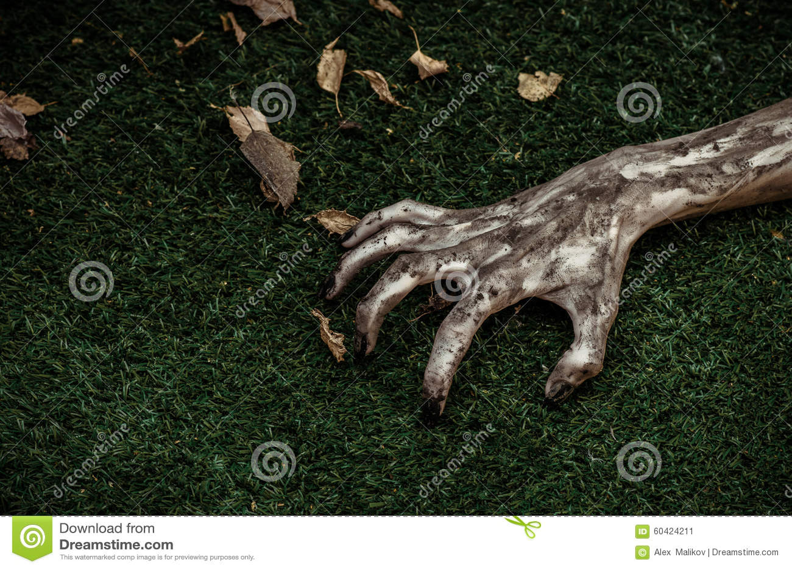 恐怖和万圣夜题材:可怕的蛇神手肮脏与黑钉子在绿草,走的死的启示,上面说谎