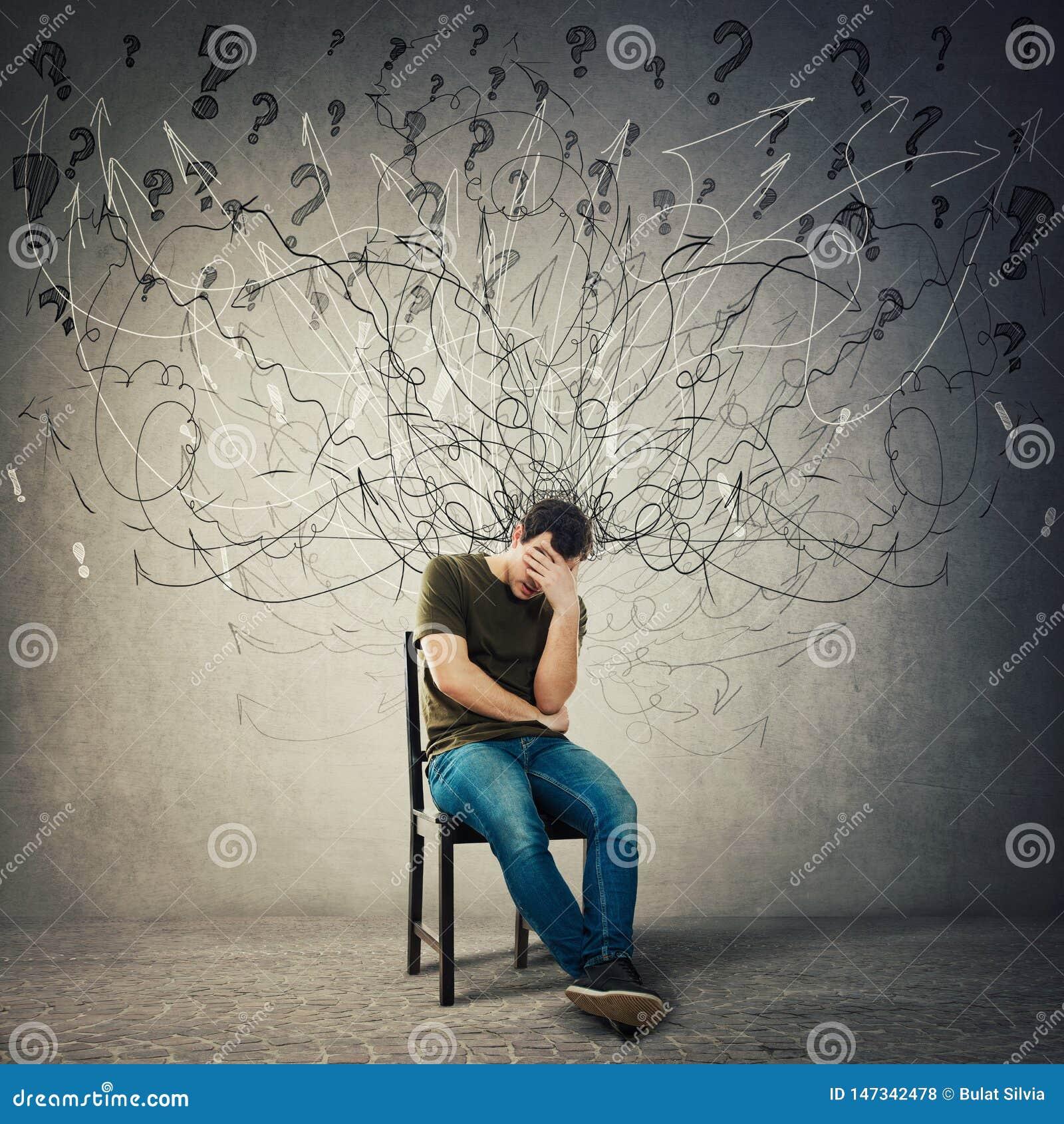 悲观,失望的人坐一把椅子在一个暗室,遭受忧虑,困厄消沉感觉