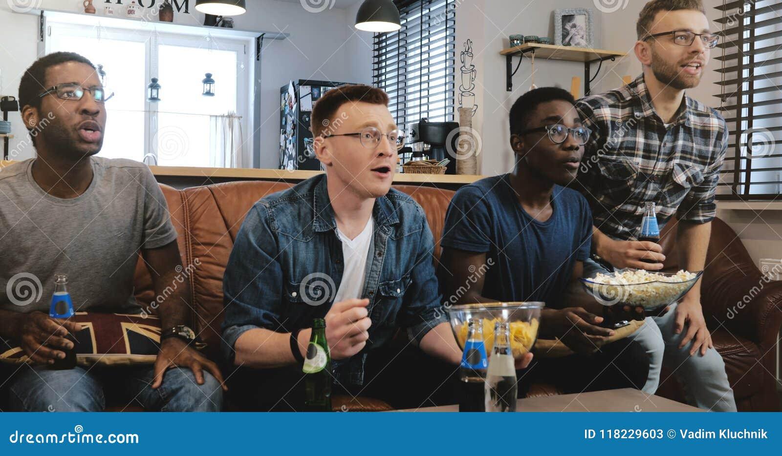 情感 在电视4K讨厌的混合的族种足球迷的非裔美国人的人手表体育庆祝在长沙发的目标用玉米花