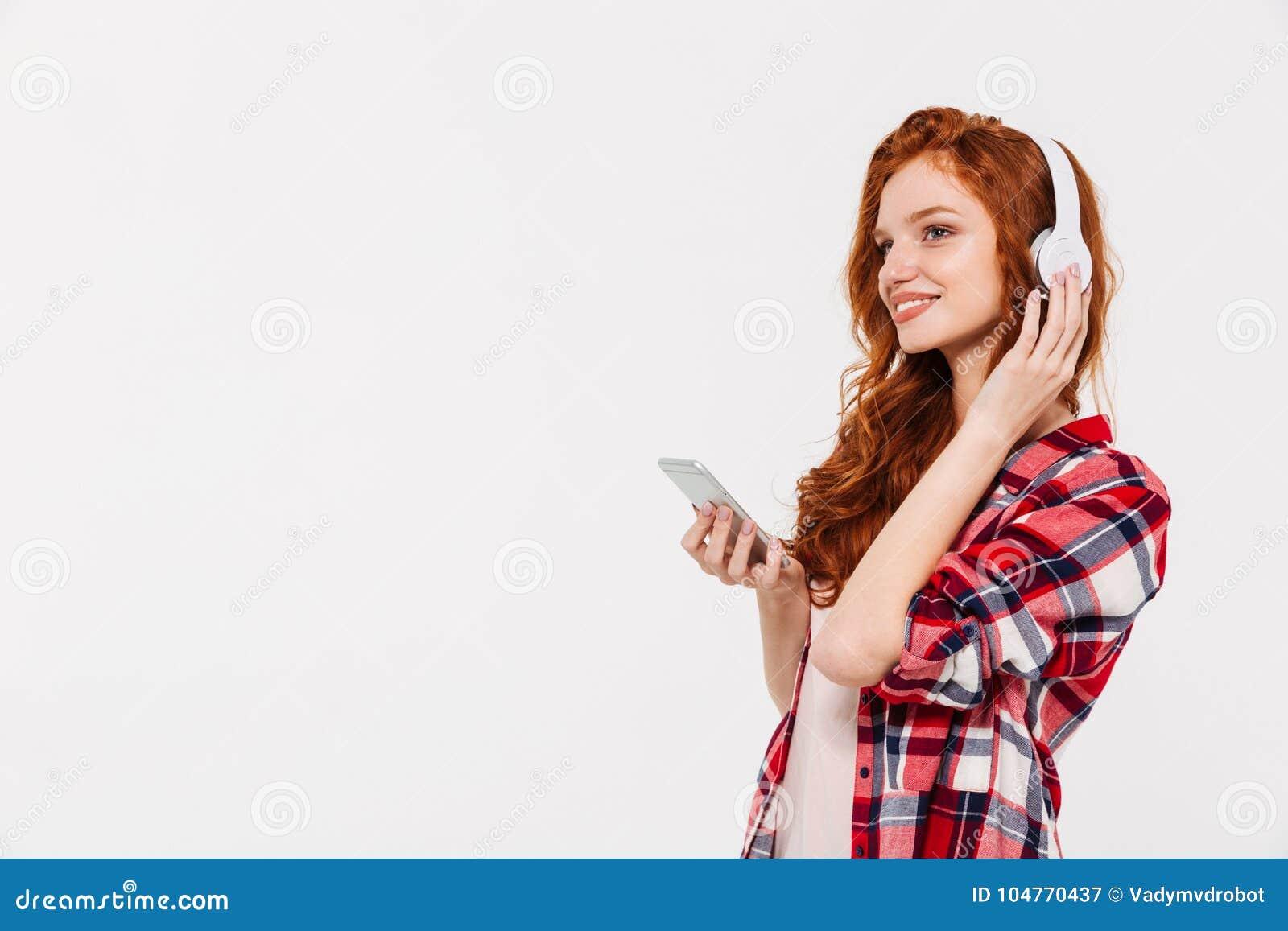 惊人的美丽的年轻红头发人夫人聊天的和听的音乐