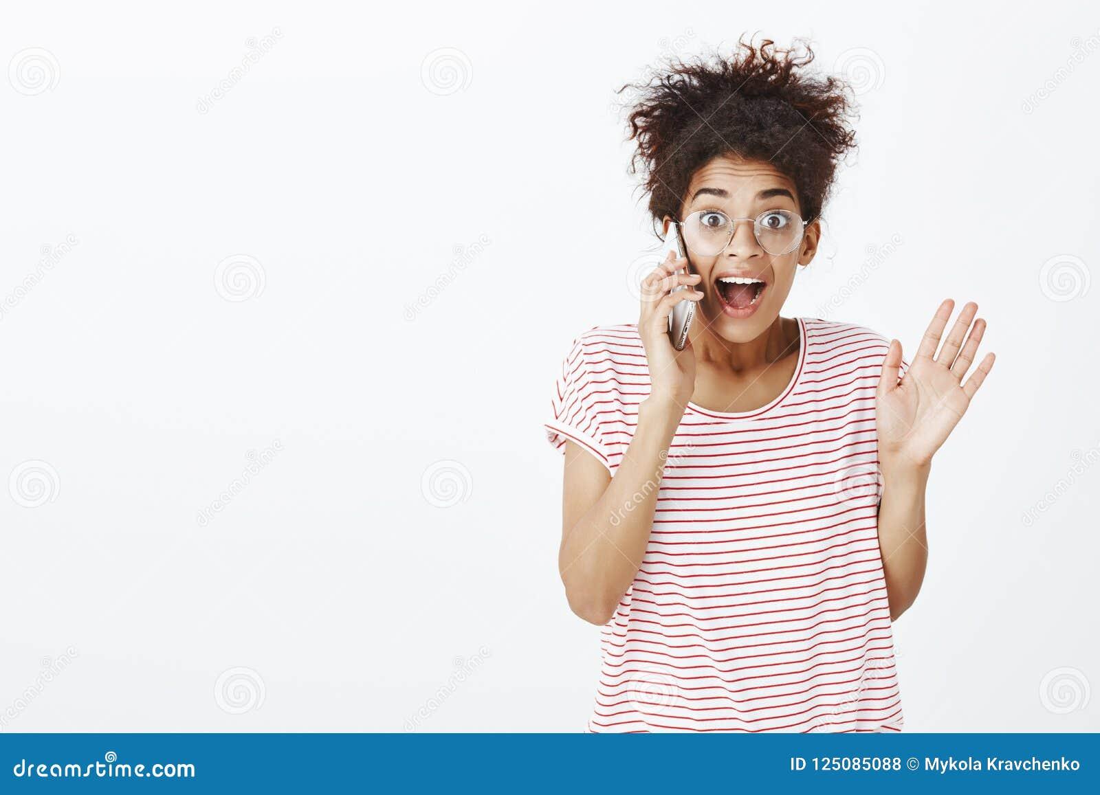 惊奇与正面新闻的女孩通过电话 喜悦的被打动的逗人喜爱的女朋友画象玻璃的和