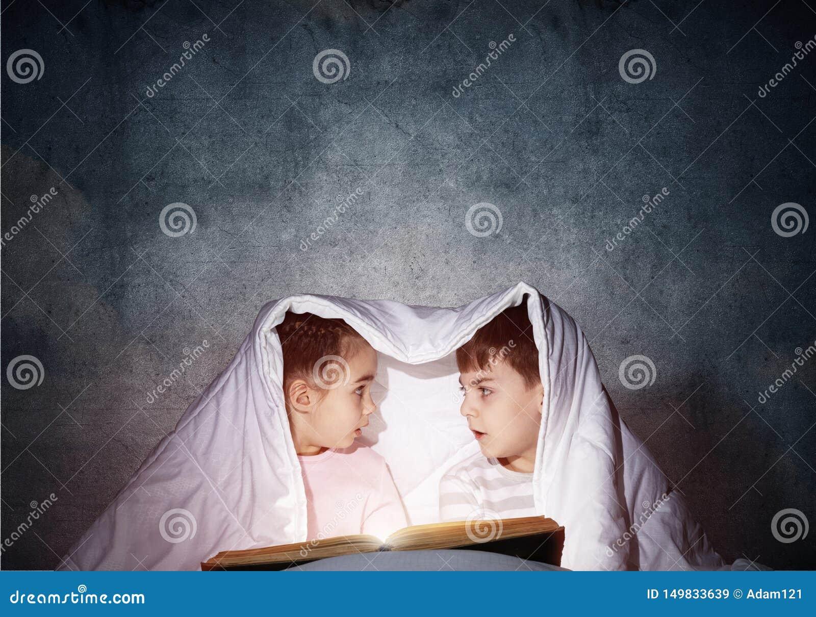 惊奇的孩子在床上的读可怕故事