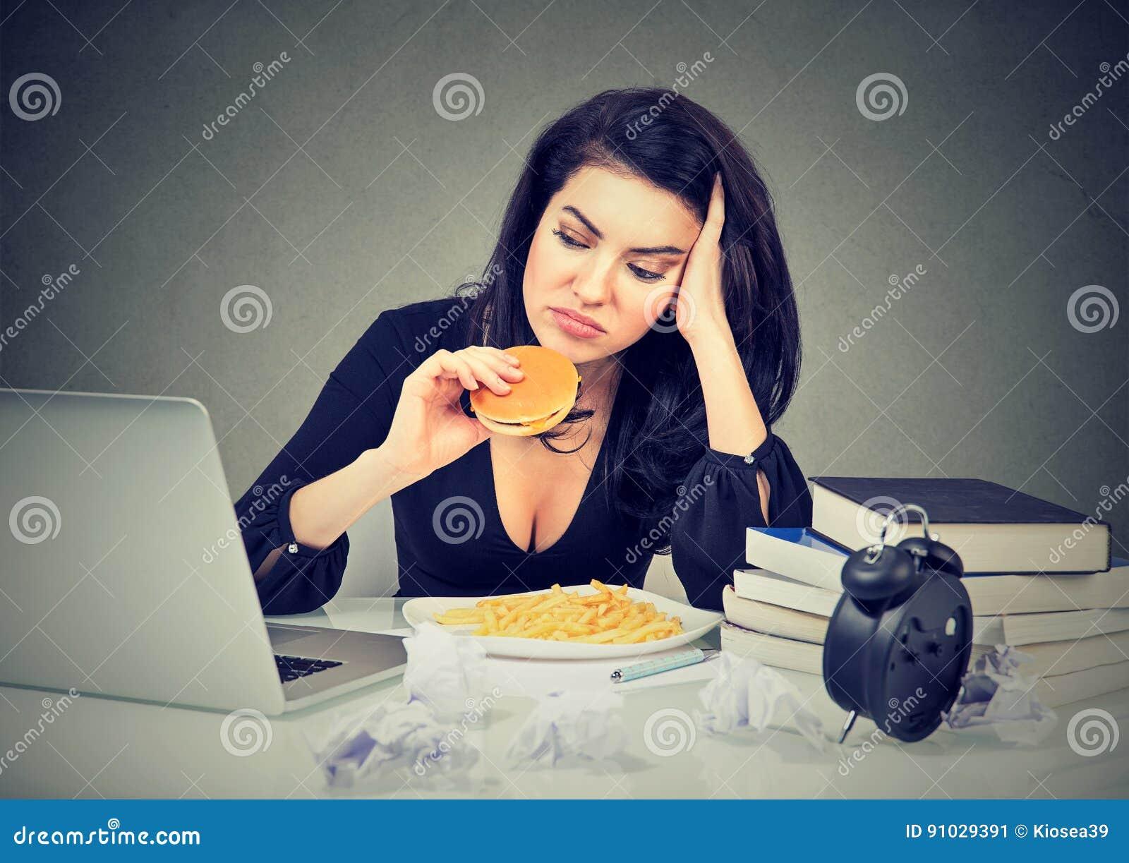 惯座生活方式和速食概念 坐在书桌的被注重的妇女吃汉堡包