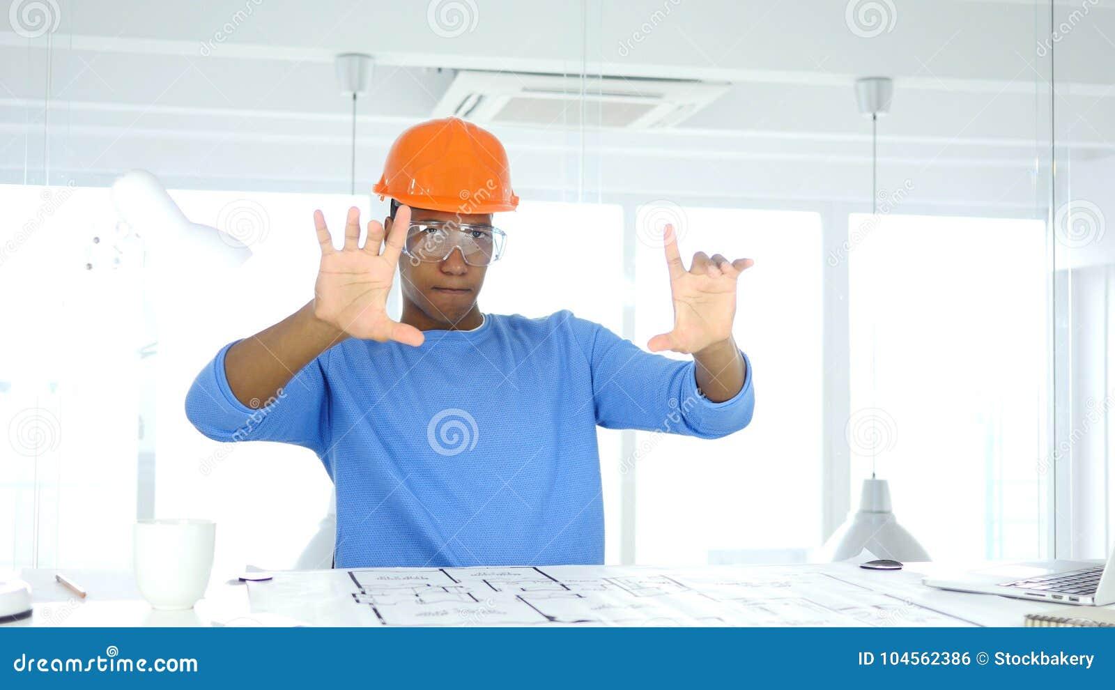 想象新的想法,在书桌上的图纸的美国黑人的工程师