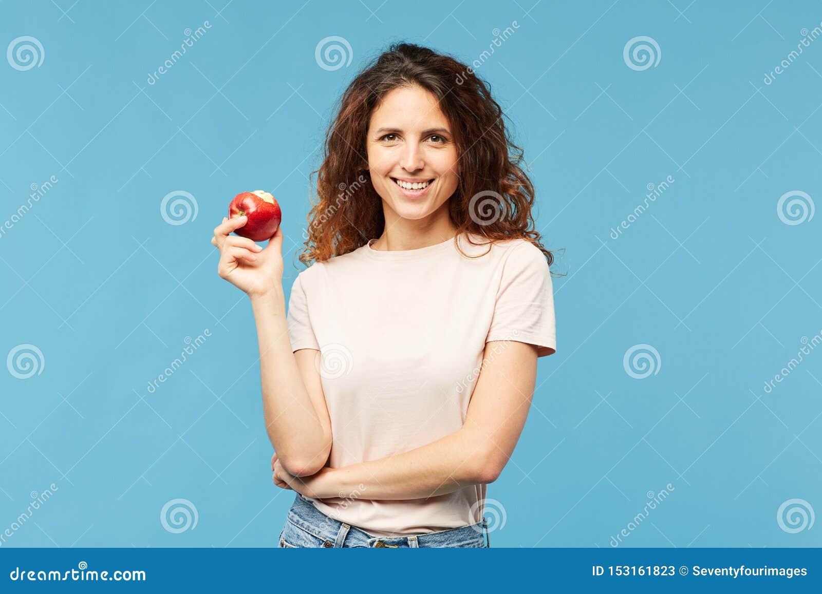 愉快和健康年轻深色的妇女用红色成熟苹果